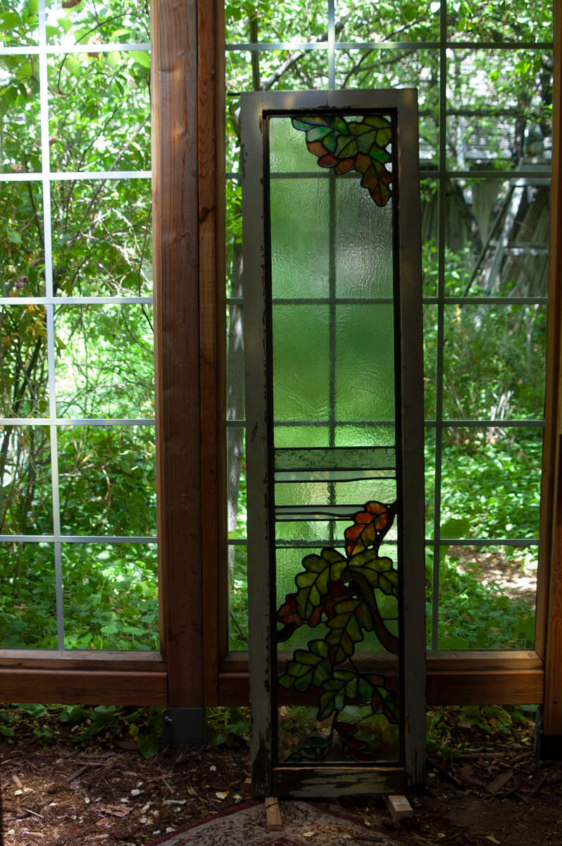 The refurbished window is returned to its wooden frame, where it is temporarily secured before being...