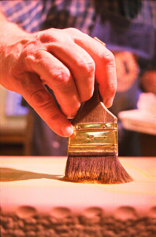 Rosin is hand-brushed over the wax images on the surface of the stone.