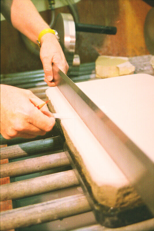 Wayne uses a metal tear bar, or straight edge, to verify that the surface of the stone is even....
