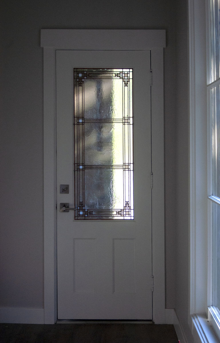 Ashton also created leaded glass for the back door (shown here) and a smaller panel for the door to ...