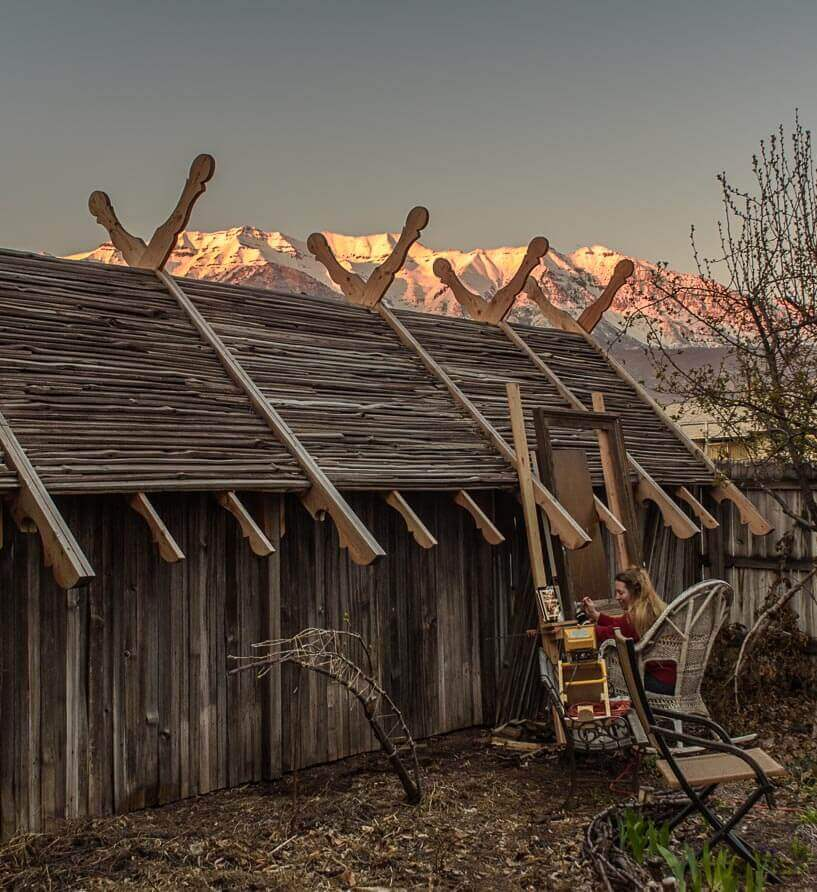 With sunset seeping up the slopes of Mount Timpanogos, Elspeth paints the chickadee on the frame whi...
